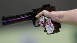 Олимпийское стрельбище и олимпийская эмблема на руке одной из участниц соревнований пистолетчиц