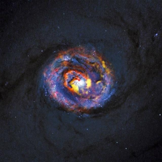 Спиралевидная форма в соседней галактике NGC 1433. Можно увидеть материал, питающий чёрную дыру, и струю вещества, выходящего из неё