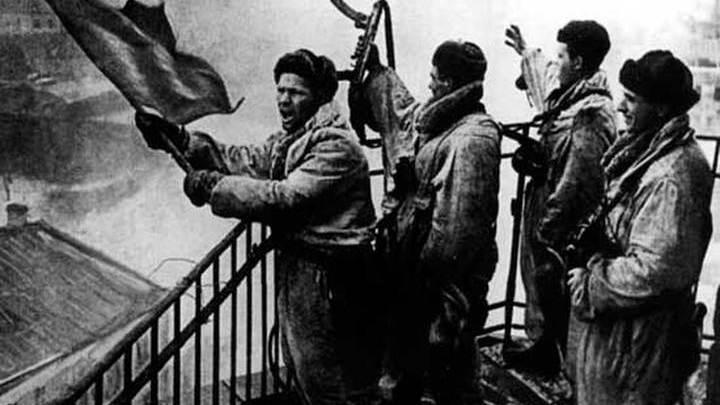 Советские солдаты поднимают красный флаг над освобожденной Гатчиной, 26 января 1944 г