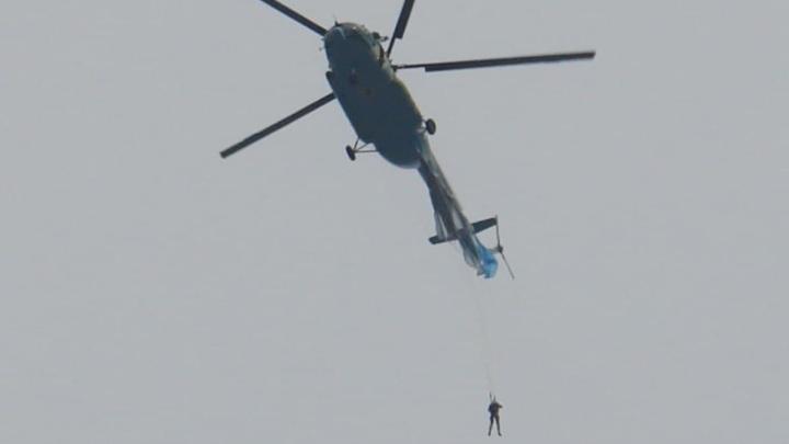 Парашютист повис на вертолете после неудачного прыжка. Видео