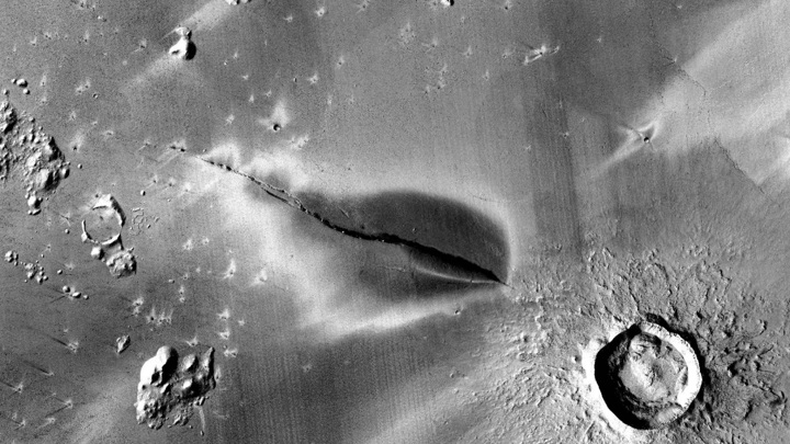 Тёмная область вокруг трещины может быть следами вулканического извержения.