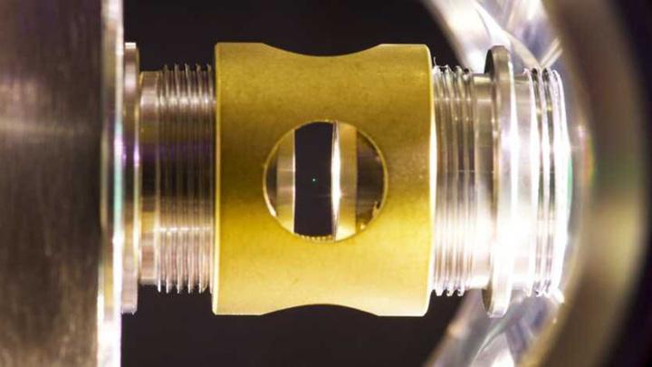 Стеклянный шар диаметром в 100 нанометров (зеленая точка в центре рисунка) парит под действием лазера.